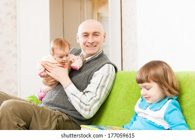 Dad and two daughters sitting on   couch.
