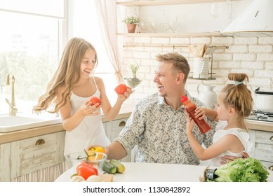 dad with two little daughters have a fun in the kitchen