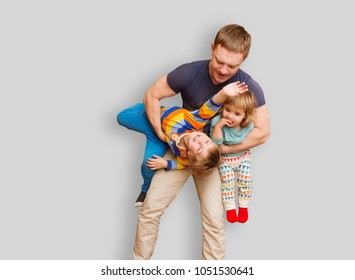 dad with two small children in his arms. The father cheerfully spends time with children.