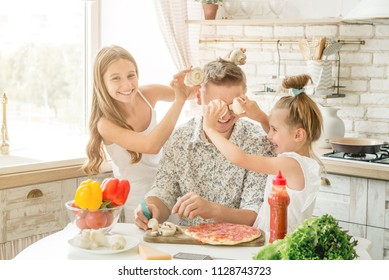 Dad with two small daughters preparing pizza with mushrooms in the kitchen
