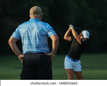 A dad watches his daughter practice her golf swing prior to a tournament.