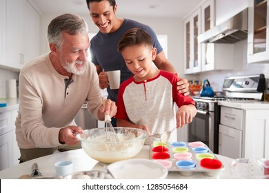 Dad watching his son making cakes with grandad at the kitchen table, close up