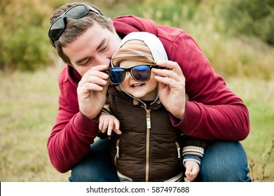 Dad wears sunglasses to his young son. Father plays with the baby.