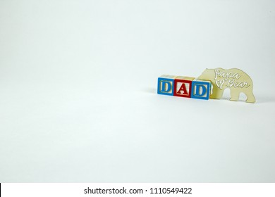 Dad word spelled with blocks and unfinished wood bear
