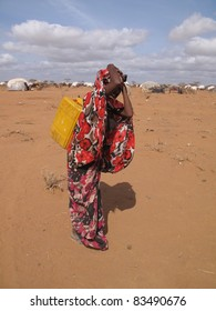 DADAAB, SOMALIA-AUGUST 15: Unidentified woman hauls water to the Dadaab refugee camp where thousands of Somalis wait for help because of hunger on August 15, 2011 in Dadaab, Somalia.
