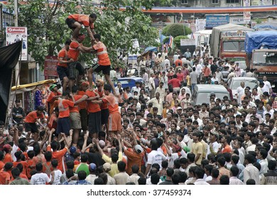 DADAR, MAHARASHTRA / INDIA - AUGUST 24, 2008 : A GROUP OF MEN BUILDING A HUMAN TOWER, TO CATCH AND BREAK THE POT, FILLED WITH BUTTER, ON DAY OF CELEBRATION OF HINDU FESTIVAL JANMASTAMI IN INDIA.