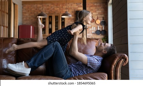Daddy, I can fly like a plane! Affectionate joyful young father lying on sofa at living room raising up to air overjoyed laughing small school age daughter playing airplane or trapeze artists together