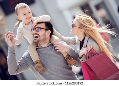 Daddy carries his son on his shoulders. Family resting in the city on sunny day.