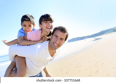 Daddy carrying children on his back at the beach