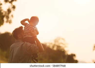 Daddy carrying son on his back at the sunset.