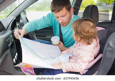 Daddy and child are traveling. Father and daughter are looking on the map route