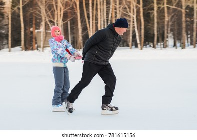 Daddy and daughter skate on the rink under the open sky on a winter evening