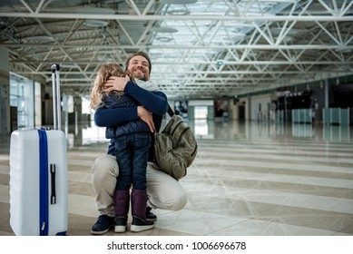 Daddy is embracing girl in the airport hall with happiness. Copy space in right side