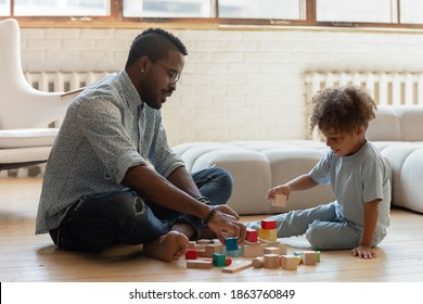 Daddy having day off. Happy friendly afro american family father and little preschool kid son spending leisure time together playing interesting games, learning and developing mind in useful activity