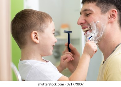 Daddy and his child son shaving and having fun in bathroom