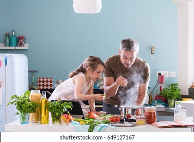 Daddy and his little daughter cooking a recipe in the kitchen, there is steam escaping from the pan on cooking plate