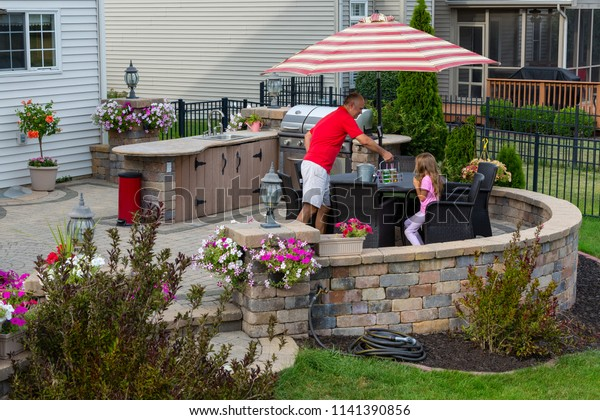 Daddy serving lemonade to his little daughter outdoors on a brick patio as she relaxes in the shade of an umbrella near an outdoor kitchen and gas barbecue in summer
