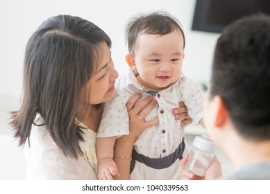 Daddy showing milk bottle to baby. Happy Asian family at home, candid living lifestyle indoors.