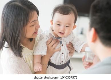 Daddy showing milk bottle to baby boy. Happy Asian family at home, candid living lifestyle indoors.