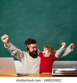 Daddy and son raising clenched fists in hooray gesture. Hooray. Family business. Chalkboard background. Family business run by his father. Concept of education and teaching