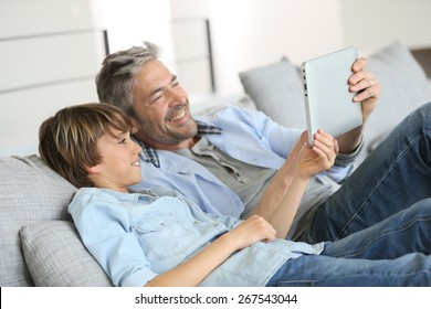 Daddy and son websurfing on digital tablet at home