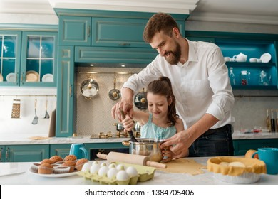 Daddy teaching child to bake. Smiling girl blending ingredients with a whisk. Leisure, cooking classes with parents.