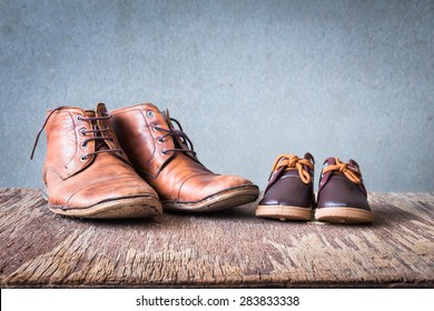 Daddy's boots and baby's shoes, fathers day concept.