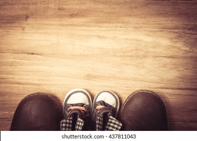 Daddy's boots and baby's sneakers, on wood background, fathers day concept.vintage color