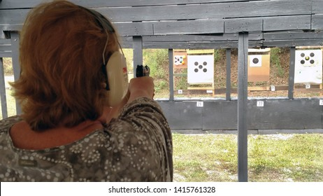 Dade City, Florida - 10/18/2015: Woman shooting semi-automatic pistol at the Dade City Rod and Gun Club range