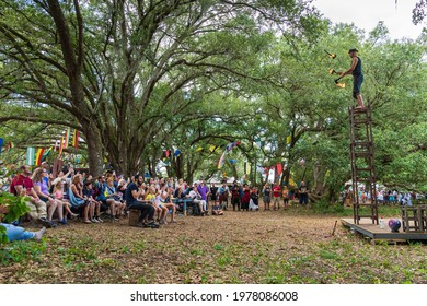 DADE CITY, FLORIDA, USA - MAY 22, 2021: Ichabod Wainwright juggles flaming axes while standing on stacked chairs at the Bay Area Renaissance Festival, Withlacoochee River Park
