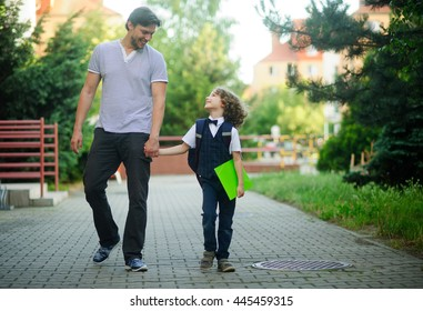 Dad's taking a first grader to school. He holds his son's hand. Little schoolboy is smartly dressed. Behind the boy's backpack. Student with love and trust looking for my father. Back to school.