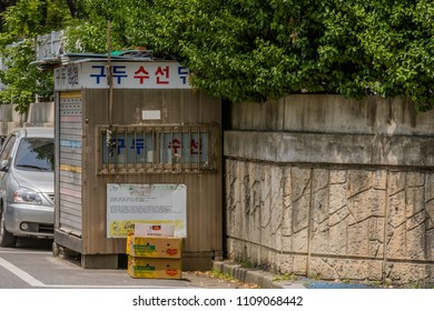 Daejeon, South Korea; June 8, 2018; Small metal building that was once used as a shoe repair shop shuddered and sitting next to concrete wall.