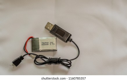 Daejeon, South Korea; March 26, 2017: Closeup of individual drone battery with usb charging cable on white background.