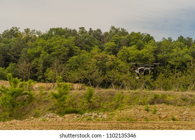 Daejeon, South Korea; May 22, 2018: DJI Inspire 1 Version 2 drone hovering above ground in front of grove of trees.