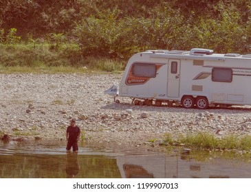 Daejeon, South Korea; September 23, 2018: Unidentified Korean man wearing shorts and t-shirt wading in river next to rocky shore where a camper is parked.