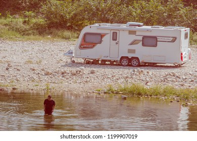 Daejeon, South Korea; September 23, 2018:Daejeon, South Korea; September 23, 2018: Unidentified Korean man wearing shorts and t-shirt wading in river next to rocky shore where a camper is parked.