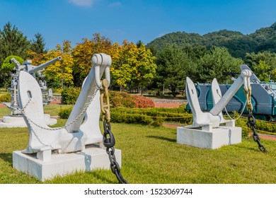 Daejeon, South Korea; September 29, 2019: Two battleship anchors in front of Three-inch fifty-caliber MK 26 navel gun on display at National Cemetery.