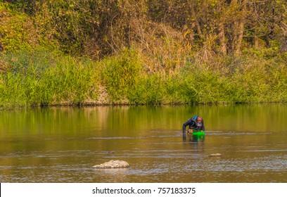 Daejeon, South Korea-November, 14,2017: Man wearing brown waders fishing near bank in Kumgang river looking into green basket
