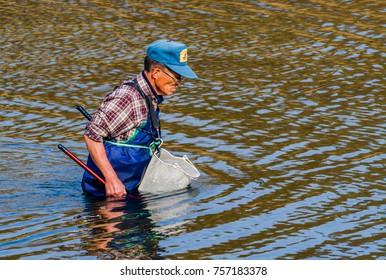 Daejeon, South Korea-November, 14,2017: Man wearing blue waders and a basket tied to his waist fishing in Kumgang river