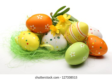 Daffodils and easter eggs on white background.