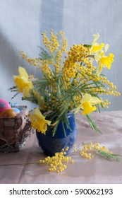 daffodils and mimosa in a blue vase and easter eggs behind a wet glass