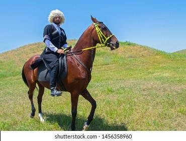 Dagestanian horseman against green steppe & blue sky. Eurasian ethnic festival 'Great Steppe' (Uly Dala), Almaty, Kazakhstan. Akhal-Teke horse. Selective focus