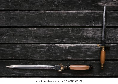 Dagger blade on aged wooden table background with copy space. Assassin weapon.