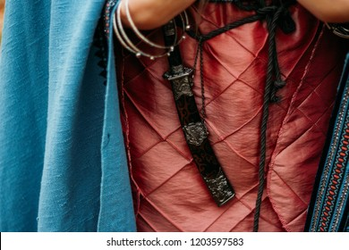the dagger in the sheath hangs on the belt of a girl in a pink dress, with a blue cape.weapon, self-defense in antiquity.