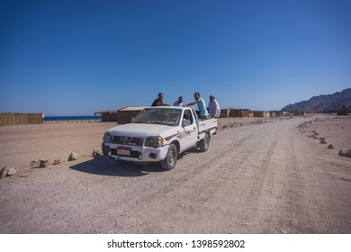 Dahab city , South Sinai , Egypt - January 11th 2018  people riding a truck in that amazing beach around Dahab in South sinai , this amazing beach in the red sea surrounded by mountains and desert.