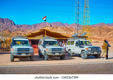 DAHAB, EGYPT - DECEMBER 16, 2017: Safari tour off roads are parked at the roadside Bedouin cafe with a viw on the rocky desert mountains on background, on December 16 in Dahab.