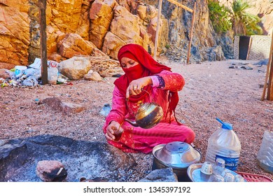 DAHAB, EGYPT - DECEMBER 16, 2017: The hospitable Bedouin  woman in traditional attire and niqab treats the tourists with hot tea, boiled on charcoal in desert, on December 16 in Dahab.