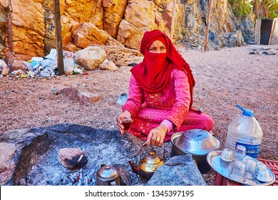 DAHAB, EGYPT - DECEMBER 16, 2017: The Bedouin  woman in bright red niqab makes hot tea, boiled on charcoal in desert, on December 16 in Dahab.