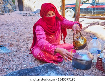 DAHAB, EGYPT - DECEMBER 16, 2017: The portrait of Bedouin woman in niqab, she, sits on the sand and pours black tea to the glass, on December 16 in Dahab.