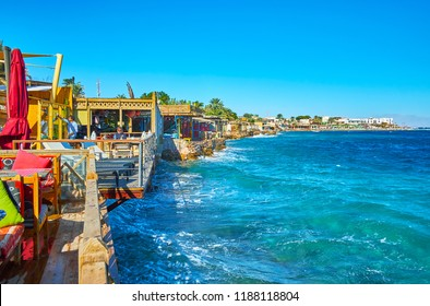 DAHAB, EGYPT - DECEMBER 25, 2017: The summer terraces of coastal cafe faces azure waters of Aqaba gulf, on December 25 in Dahab.